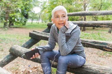 Senior Woman Relax Listening Music With Phone After Jogging In Forest. Healthy Lifestyle Workout Outdoor.
