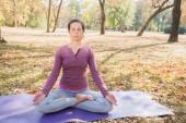 Frau, meditieren und Yoga Lotus Pose, Padmasana üben. Meditation auf sonnigen Herbsttag im Park. Training im freien.
