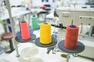 Colorful sewing threads of spools on professional machine at textile workshop stock vector