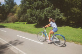 Young Woman Riding Bicycle In The Park