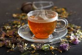 Cup of herbal tea with various herbs on dark table