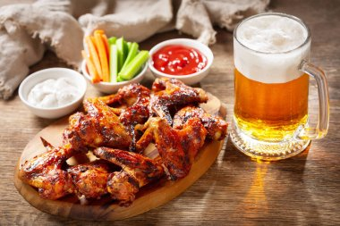 Grilled chicken wings and mug of beer on a wooden board stock vector
