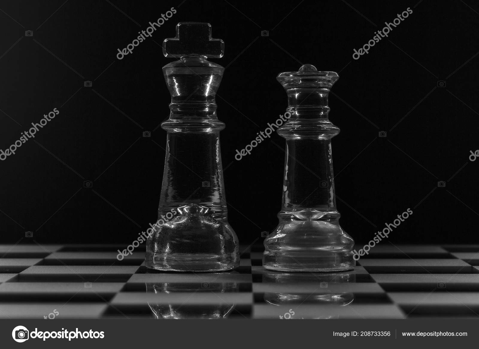 King queen glass chess pieces facing each other black white stock photo