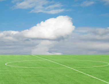 green football field against the sky with clouds