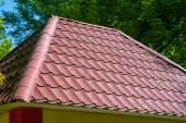 červenou taškovou střechou proti modré obloze.