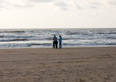 Katwijk, Netherlands - April 23, 2017: People are walking on a sunny day along the beach in Katwijk. Netherlands