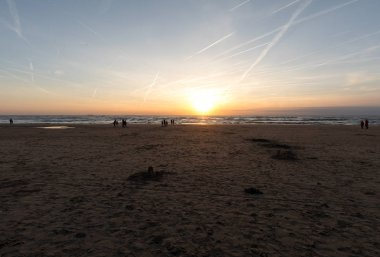 Katwijk, Netherlands - April 23, 2017: People are walking along the beach in Katwijk at sunset. Netherlands
