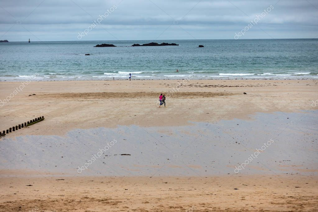 Saint-Malo, France - September 12, 2018: Women are running  along the beach in Saint-Malo, Brittany, France