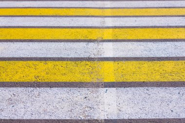 Crosswalk. Yellow and white zebra pedestrian crossing in summer during the daytime.