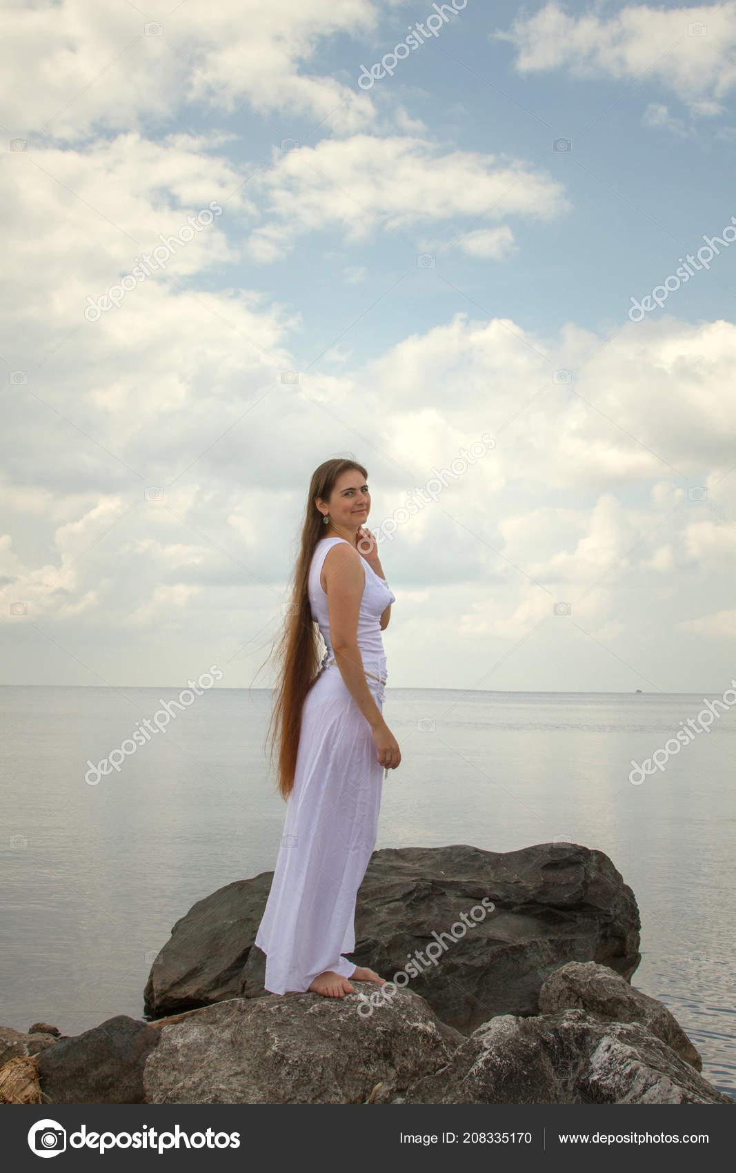 d78264f1c739 Bella ragazza con capelli lunghi e vestito bianco in riva al mare — Foto di  ...