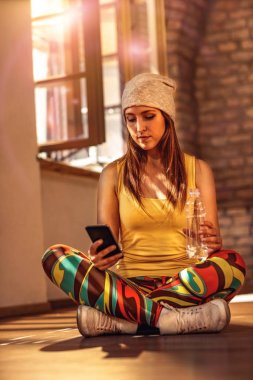 Smiling urban girl holding smartphone texting messaging