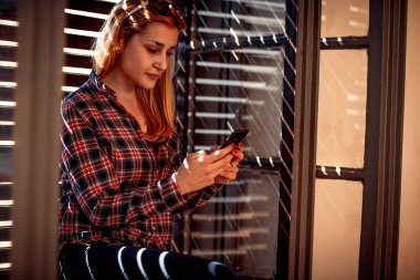 Young urban girl holding a cellphone and texting messaging