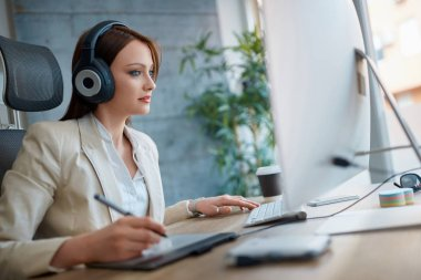 Young woman wearing headphones and working in design studio