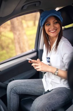 Smiling woman listening to music with headphones moving in car