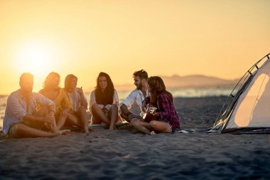 Group of young friends with guitar at beach. friends relaxing on sand at beach with guitar and singing on beautiful summer sunset