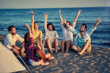 Summer, holidays, vacation, music, happy people concept group of smiling friends with guitar having fun on the beach together