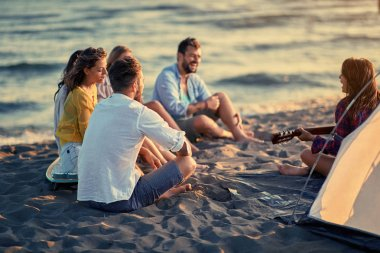 Summer, holidays, vacation, music, happy people concept group of smiling young friends with guitar having fun on the beach together