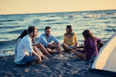 Summer, holidays, vacation, music, happy people concept group of smiling young friends with guitar having fun on the beach