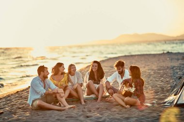 Group of young friends with guitar at beach. friends relaxing on sand at beach with guitar and singing together