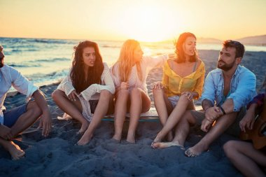 Group of happy young friends having a great time together at the beach