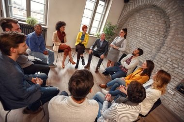 business woman talking to group of colleagues in circle and discussing