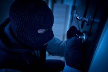 burglar or thief breaking the lock of a door