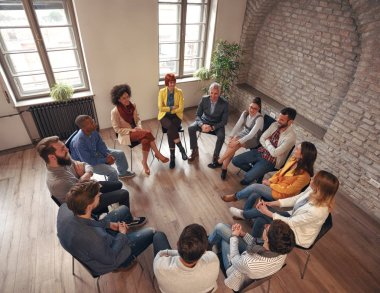Group of business people sitting at circle in board room and discussing