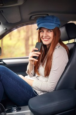 Happy young girl in headphones with smartphone listening to the music in the car