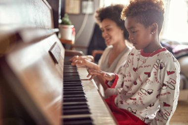 Little girl is playing on piano x-mas music. Concept Christmas, New Year, holiday, family happiness, childhood