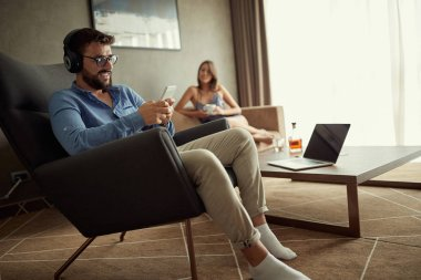 Smiling man uses a phone with headphones to listen to music and relax at home