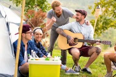 Tattooed guy play guitar and smile with friends