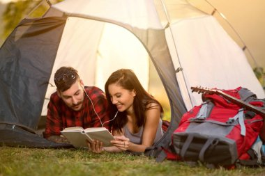 couple in tent reading a book