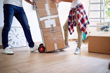 New home - Man and woman with cardboard boxes while moving in house