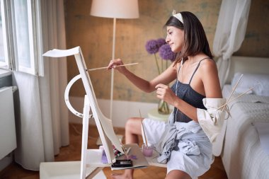young sexy artist relaxing with painting in her bedroom