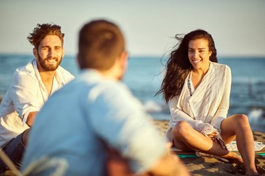 Happy young people sitting on the beach singing and playing guitar