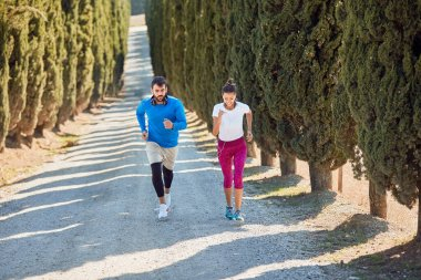young caucasian couple jogging uphill on a gravel road with trees and a car following them. professional, personal, trainer