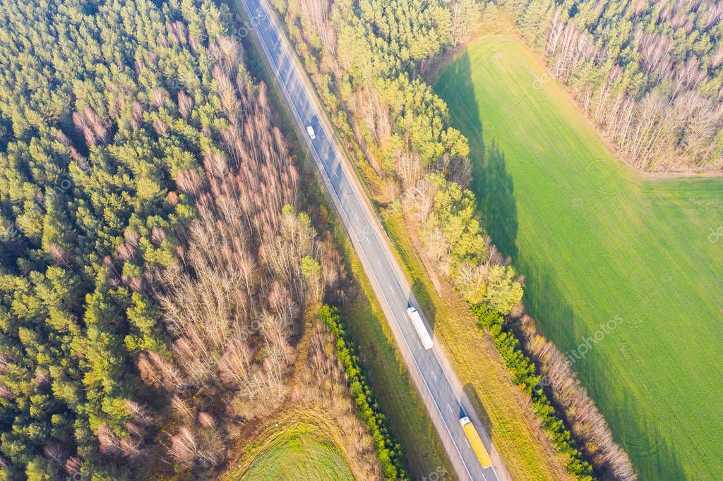 Highway surrounded by green forest. Autumn areal landscape