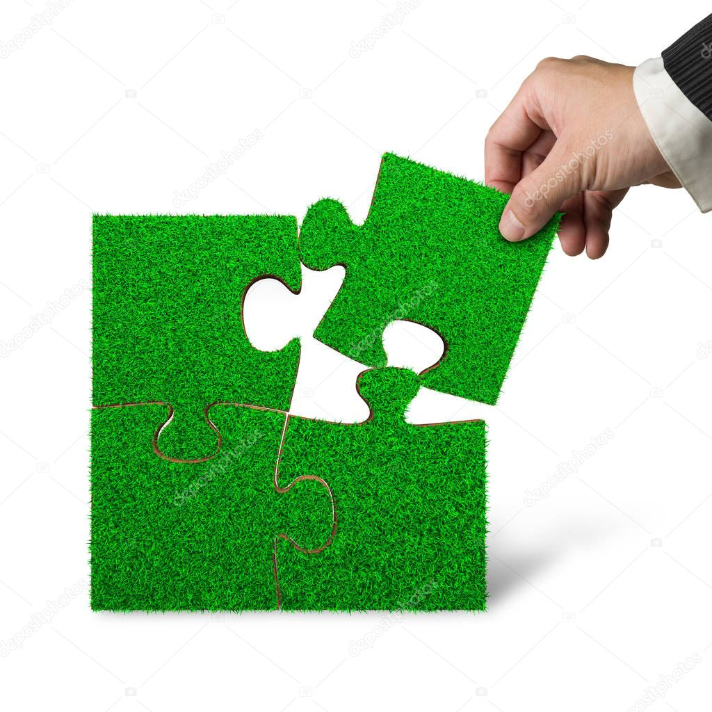 Male hand put the last piece of green grass jigsaw puzzle to complete, isolated on white background.
