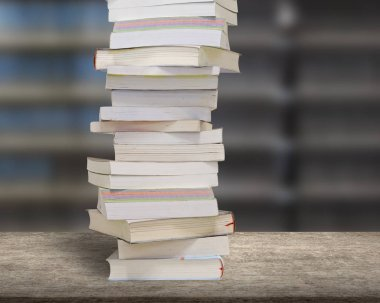 Stacking books on wood desk with blur bookshelfs background.