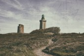 Photo Noisy , vintage style image of a footpath leading to the lighthouse from Cap de Frehel on Armor Coastline in Brittany in North of France.