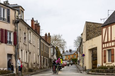 Dampierre-en-Yvelines, France - March 4, 2018: The breakaway (Pierre Rolland, Jurgen Roelandts,Pierre-Luc Perichon) passing in front of a traditional half timbered house during the stage1 of Paris-Nice 2018.
