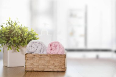Towels on wooden table with copy space on blurred bathroom backg