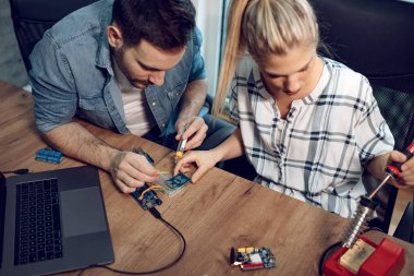 Two young business partners technician focused on repairing of electronic equipment