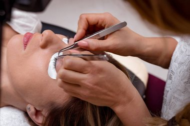 Close view of beautician applying extended eyelashes to young woman