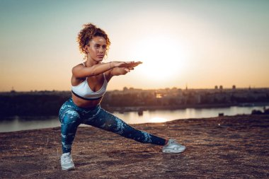 Young sporty woman doing stretching exercises by river at sunset