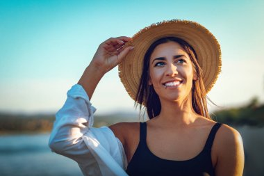 Portrait of young woman in straw hat relaxing at sunset time on river bank