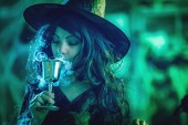 Mladá čarodějnice s vážnou tváří drží pohár a pít kouzelný lektvar