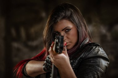 Woman standing in attitude of aiming and looking through sight automatic rifle