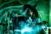 čarodějnice v strašidelné okolí a kouřově zelené pozadí držící magický nápoj v poháru