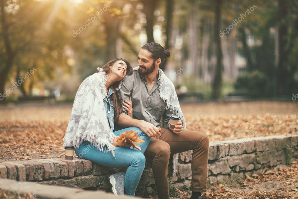 smiling couple sitting on stone fence and drinking coffee in autumn park
